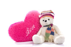 Toy teddy bear sitting with heart-shaped pillow Royalty Free Stock Photography