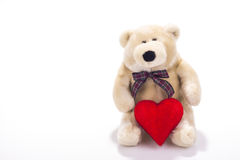 Toy teddy bear sitting with valentine heart. Teddy bear sitting with valentine heart isolated on white royalty free stock photography