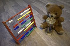 Toy teddy bear with timeglass and childrens calculator Royalty Free Stock Images