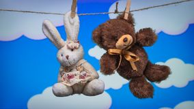 Toy Teddy draagt en het konijn wordt opgeschort van de kabelwasknijpers op een achtergrond van beeldverhaal witte wolken stock afbeeldingen
