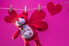 Toy Teddy draagt met documenten harten wordt opgeschort van de kabelwasknijpers op een achtergrond van beeldverhaal witte wolken stock afbeelding