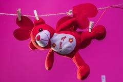 Toy Teddy draagt met documenten harten wordt opgeschort van de kabelwasknijpers op een achtergrond van beeldverhaal witte wolken royalty-vrije stock foto's