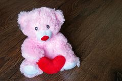 Toy teddy with heart isolated on wooden background stock images