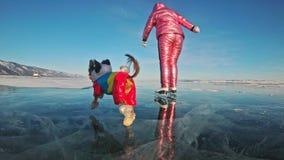 Toy Terrier en ropa divertida y zapatos divertidos juega con la bola en el hielo hermoso en grietas Mamá e hija en deportes