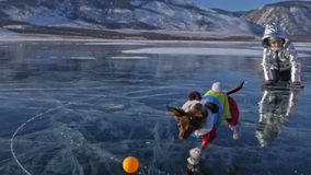 Toy Terrier en ropa divertida y zapatos divertidos juega con la bola en el hielo hermoso en grietas Mamá e hija en deportes almacen de metraje de vídeo