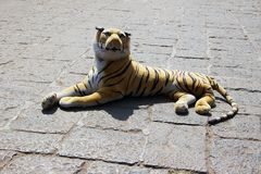 Toy tiger reclining on pavement Royalty Free Stock Image