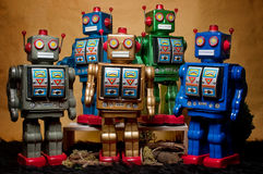 Toy Tin Robot Gathering 07. Toy tin robot gathering on brown background Royalty Free Stock Photos