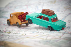 Toy tow truck with a car in tow. Vintage toy tow truck towing a toy car on a map Royalty Free Stock Photos