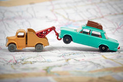 Toy tow truck towing a toy car. Vintage toy tow truck towing a toy car on a map Royalty Free Stock Photo