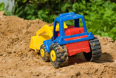 Toy tractor. Children's multi-coloured plastic tractor on sand Royalty Free Stock Photography