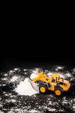 Toy tractor clears snow pile Stock Images