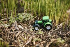 Toy tractor on green grass background . Spring sowing works royalty free stock image