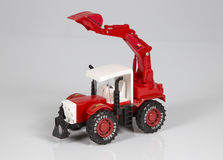Toy tractor. Red tractor toy on a white background Royalty Free Stock Photography