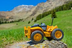 Toy tractor on rock in mountain Stock Photo