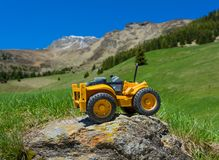 Toy tractor on rock in mountain. Small toy tractor on rock in mountain Royalty Free Stock Photography