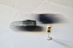 Toy traffic light and cars passing. Transportation Stock Photo