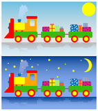 Toy train. Two trains with presents. Day and night Royalty Free Stock Photography