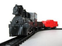 Toy train. Toy steam engine with caboose and coal tender on tracks stock photography