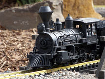 Toy Train. Model train emerging from a trestle running around a track royalty free stock images