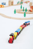 Toy train with cars and wooden toy railway with spruces. On white background. Focus on train Royalty Free Stock Photo
