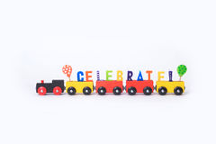 Toy train with colorful letters on top arranged in word celebrat Royalty Free Stock Photos