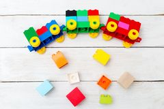 A toy train of cubes of lego and wooden blocks on a wooden backg. Round Stock Images
