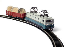 Toy train with euro. Toy train and railroad with two euro coins Royalty Free Stock Photos