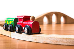 Toy train made of wood with bridge in backdrop Stock Photography