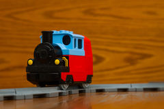 Toy train rides on rails. The toy train goes on rails. On a brown background Royalty Free Stock Photo