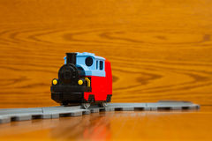 A toy train rides on rails. The toy train goes on rails. On a brown background Royalty Free Stock Photography