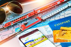 Toy train, tickets, passport and bank card on laptop or notebook Stock Photos