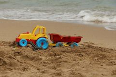 Toy traitor with trail on the beach. Children's toy on the sand Royalty Free Stock Photography