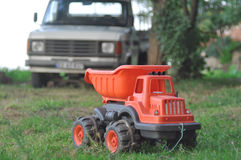 Toy truck. In front of a real vehicle Royalty Free Stock Photo
