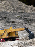 Toy Truck. Close up of an old toy backhoe in a sandbox Royalty Free Stock Photo