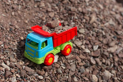 Toy truck against a backdrop of sand and stones Royalty Free Stock Images