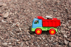 Toy truck against a backdrop of sand and stones Royalty Free Stock Photos