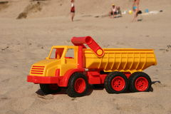 Toy Truck on the beach. In front of a group of people stock photography