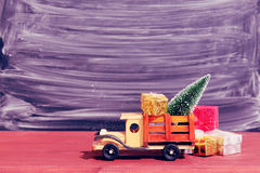 Toy truck carries gifts and a Christmas tree. Photo in vintage style Royalty Free Stock Images