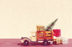 Toy truck carries gifts and a Christmas tree. Photo in vintage style Stock Photo