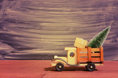 Toy truck carries gifts and a Christmas tree. Photo in vintage style Stock Photography
