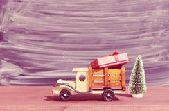 Toy truck carries gifts and a Christmas tree. Photo in vintage style Royalty Free Stock Photo