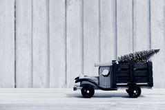 Toy truck carries gifts and a Christmas tree. Photo in vintage style Stock Photos