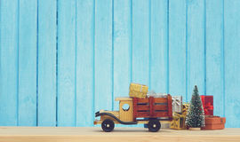 Toy truck carries gifts and a Christmas tree. Photo in vintage style Royalty Free Stock Photography
