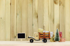 Toy truck carries gifts and a Christmas tree. Photo in vintage style Stock Images