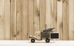 Toy truck carries gifts and a Christmas tree. Photo in vintage style Royalty Free Stock Photos