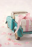 Toy truck carrying a gift box with pink ribbon Royalty Free Stock Image