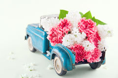 Toy truck carrying pink carnation and lilacs flowers Royalty Free Stock Image