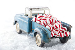 Toy truck carrying striped peppermint candy. Old blue toy truck carrying striped peppermint candy on white snowy bakcground Royalty Free Stock Photos