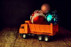 Toy truck with Christmas balls. Delivery of Christmas gifts by transport and courier service.  royalty free stock images