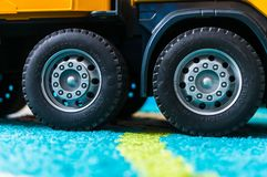 Toy truck wheels. Poznan, Poland - February 9, 2019: Close up of a plastic toy construction truck standing on a carpet in soft focus. Bruder Trackmaster brand stock photo